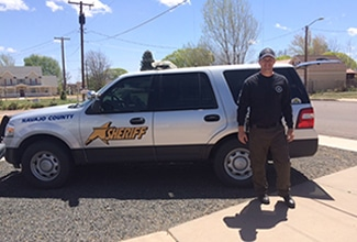 Officer standing in front of Sheriff Ford Explorer
